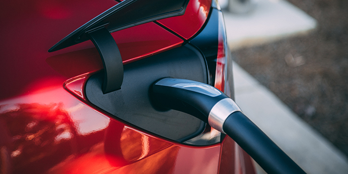 red electric vehicle plugged into charging station